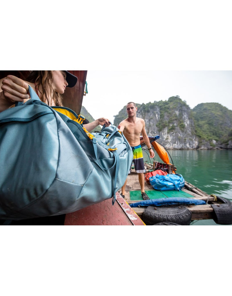 Women carrying osprey transporter 65 expedition keystone grey colour duffle bag corner view