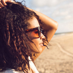BlackTravelBox | Young african american woman with glowing skin in sunglasses enjoying sun