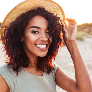 BlackTravelBox | Close up of smiling african american woman with glowing skin in summer hat