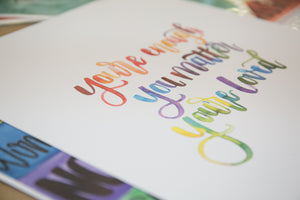 Image of Art Print with Watercolor Lettering in a Rainbow of colors that reads: You're Enough, You Matter, You're Loved.