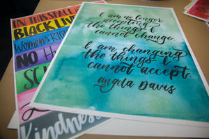 "Image of two art prints. The one on top is a mixture of green and blue watercolors. The words on top read: ""I am no longer accepting the things I cannot change. I am changing the things I cannot accept."" It sits on top of the ""In This Space"" art print."