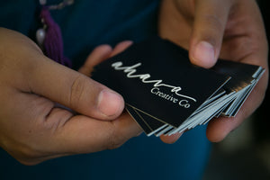 "An image of a brown woman's hands holding a stack of black business cards. They read ""Ahava Creative Co"" on the front in white."