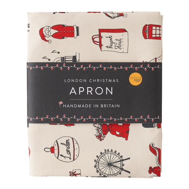 Adult's Christmas apron featuring various London Christmas icons, Red strapped London icons Christmas apron, Hand illustrated Christmas apron, Cotton Christmas apron featuring iconic London Christmas favorites, Christmas apron with repeating London Christ