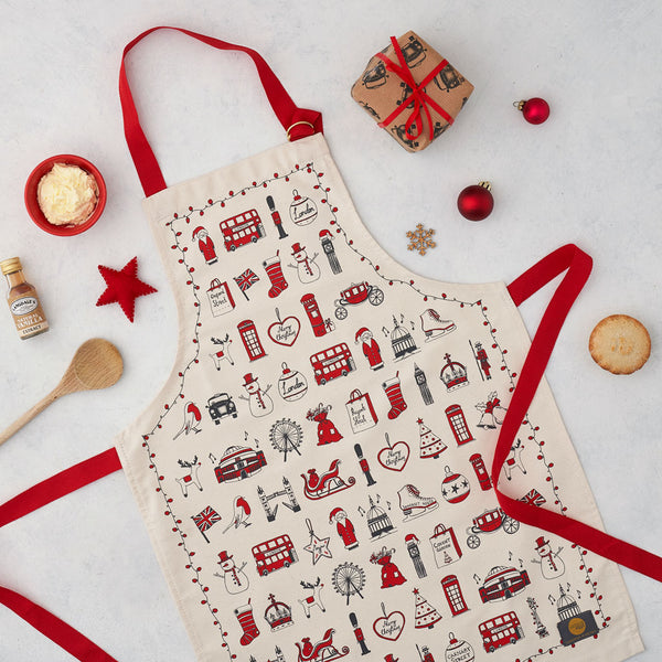 Children's London Christmas apron featuring repeating London landmarks, Kids kitchen apron featuring iconic London Christmas icons, Children's Christmas kitchen apron with red strap, Cotton Children's Christmas apron featuring ice skates and The London Eye, Children's Christmas apron featuring red and charcoal design