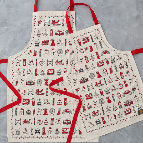 Children's London Christmas apron featuring repeating London landmarks, Kids kitchen apron featuring iconic London Christmas icons, Children's Christmas kitchen apron with red strap, Cotton Children's Christmas apron featuring ice skates and The London Ey