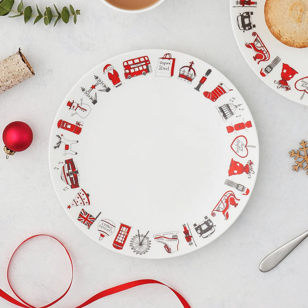 Fine bone china side plate for Christmas, Fine china side plate featuring London Christmas designs, Hand illustrated Christmas designs from London side plate, Charcoal and red London Christmas side plate, Christmas plate featuring London icons, Christmas side plate featuring Santa's sleigh and a Christmas tree, Christmas plate featuring The London Eye and Tower Bridge