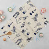 Tea towel featuring repeating nautical icons design in navy, Hand illustrated nautical tea towel featuring repeating pattern of navy nautical icons, Kitchen towel featuring nautical design in navy, Nautical dish towel featuring repeating pattern of beachscapes