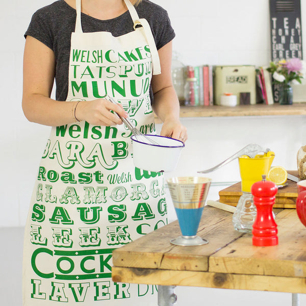 Apron featuring repeating design of black typography of traditional Welsh dinner items, Unisex kitchen apron featuring typography of traditional Welsh meal items, Welsh kitchen apron featuring repeating pattern from traditional dinners