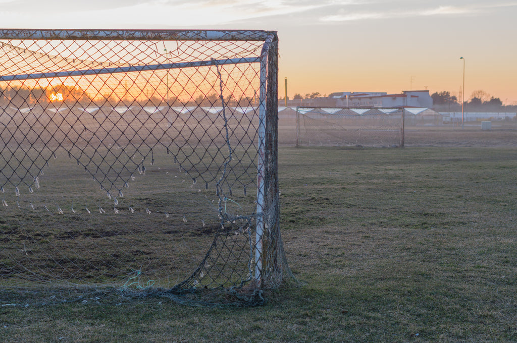 Net or goal on a field of grass with a sunset.