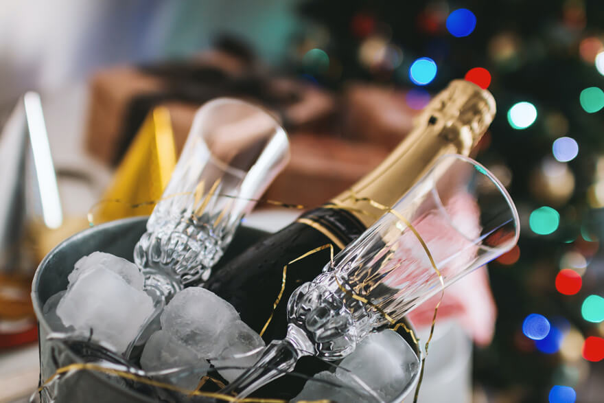 A bottle of champagne, glasses, and ice in a bucket