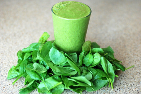 A green smoothie surrounded by leafy greens