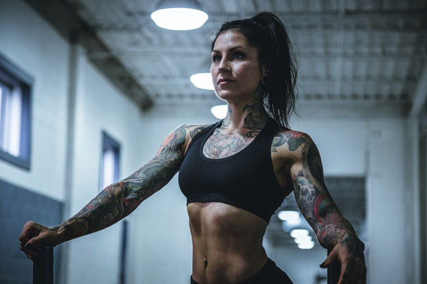 Tattooed woman exercising at the gym