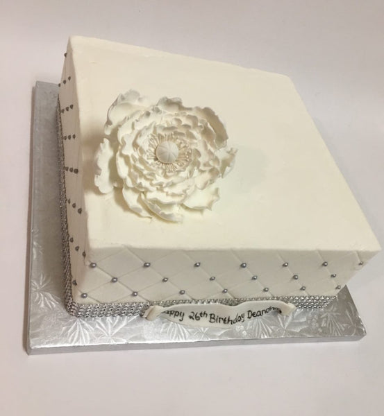 White 1-tier square birthday cake with pearl sides and flower