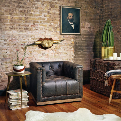 Austin by Stash Home leather tufted swivel chair in front of exposed brick