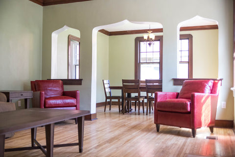 Red leather chairs in the living room at the Mercy House furnished by Stash Home in Memphis TN