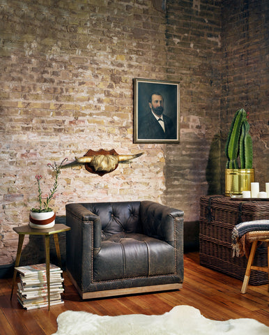 Stash Home leather tufted chair against exposed brick wall with small side table on sale for Presidents' Day
