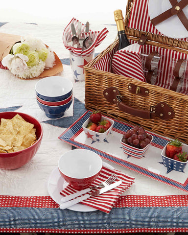 Quilt topped with red, white, and blue cups and serving dishes