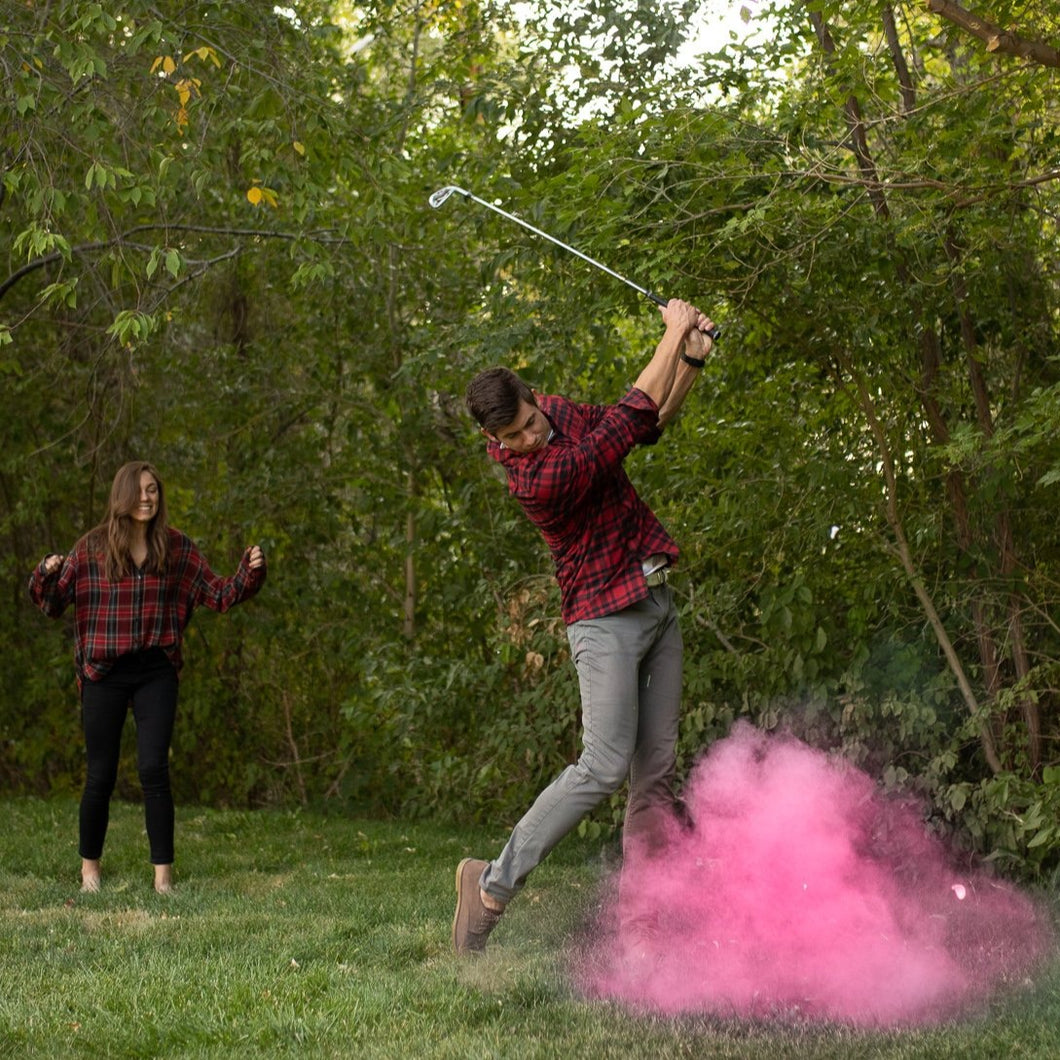 man hitting gender reveal golf ball exploding with pink colored powder. available in pink or blue with non-toxic, biodegradable powder