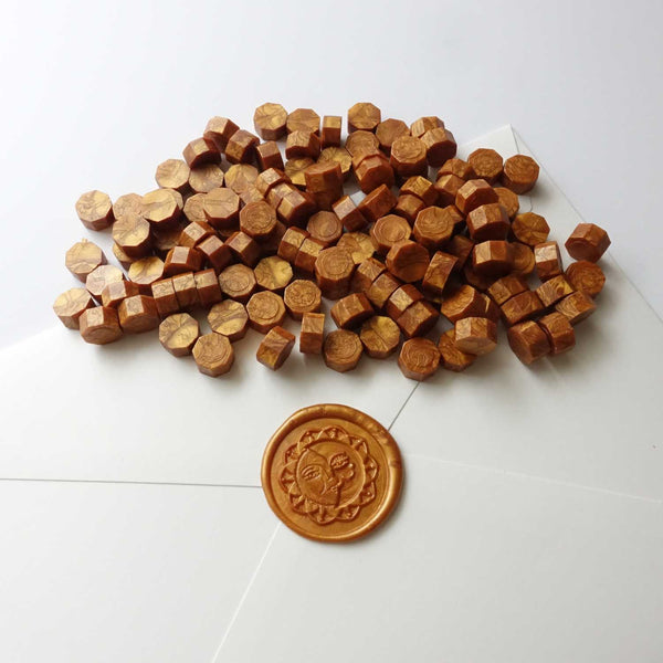 Amber gold sealing wax beads with sun wax seal on envelope