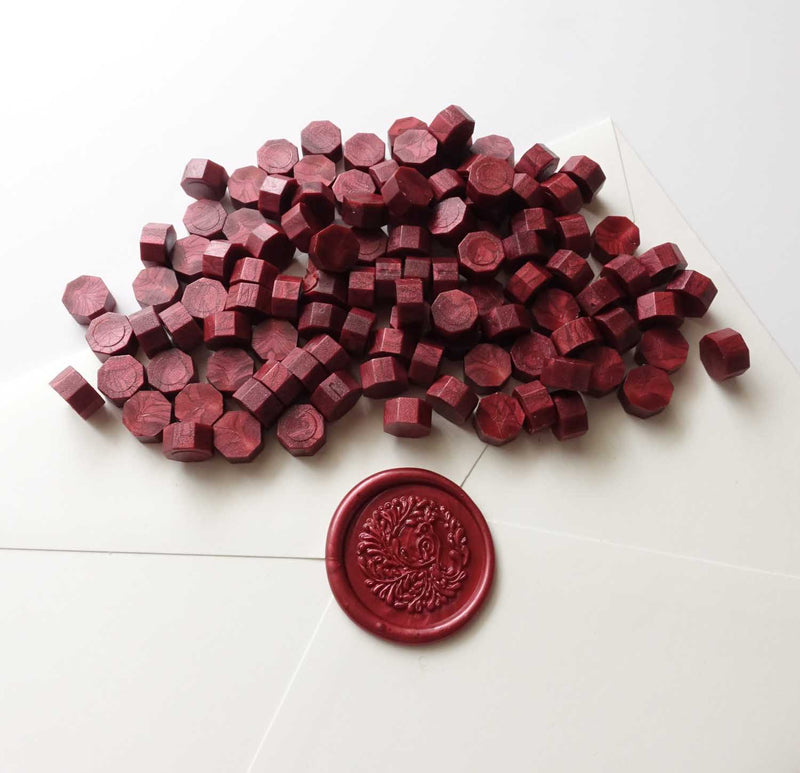 Burgundy wax beads pellets granules with song bird wax seal on white envelope
