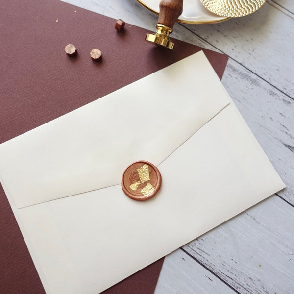 Wax seal on envelope with gold leaf and blank stamp plus wax beads