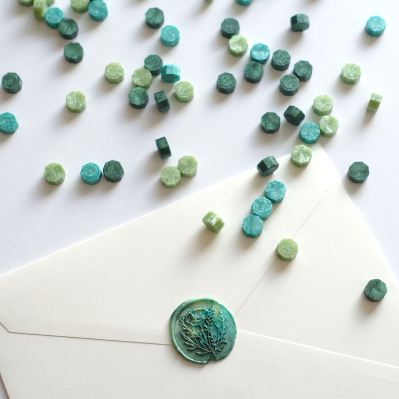 Mixed green wax beads pellets granules with wild flower wax seal on white envelope