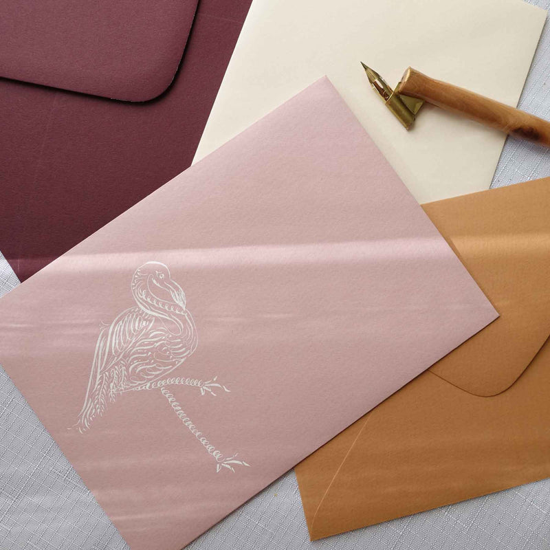 Flamingo animal calligraphy flourishing on pink and terracotta envelope