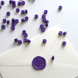 Purple wax beads pellets granules with for you wax seal on white envelope