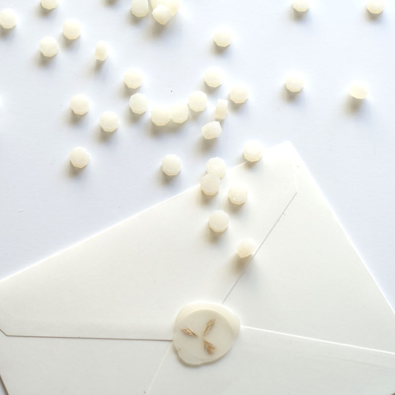 Semi transparent vellum wax beads pellets granules with wax seal on white envelope