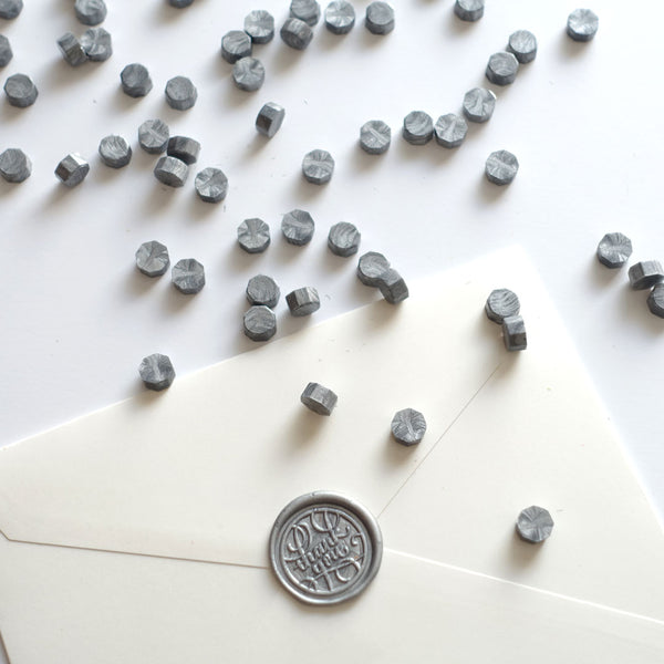 Silver wax beads pellets granules with thank you wax seal on white envelope