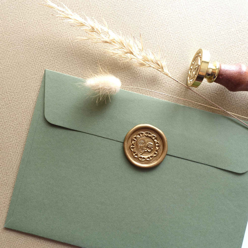 Antique gold half sun and crescent moon wax seal stamp on olive green envelope