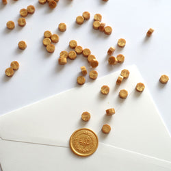 Yellow gold wax beads pellets granules with monogram wreath wax seal on white envelope