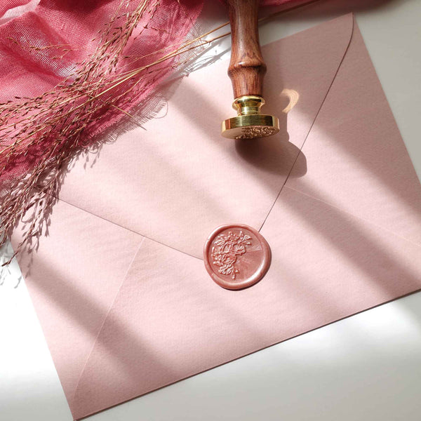 Dusty rose half garland wax seal on wedding invitations envelope