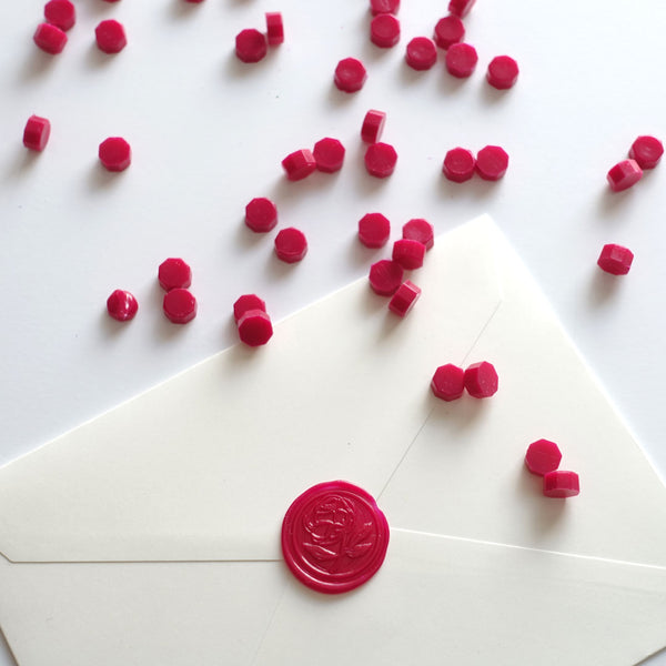 Plum red wax beads pellets granules with peony rose flower wax seal on white envelope