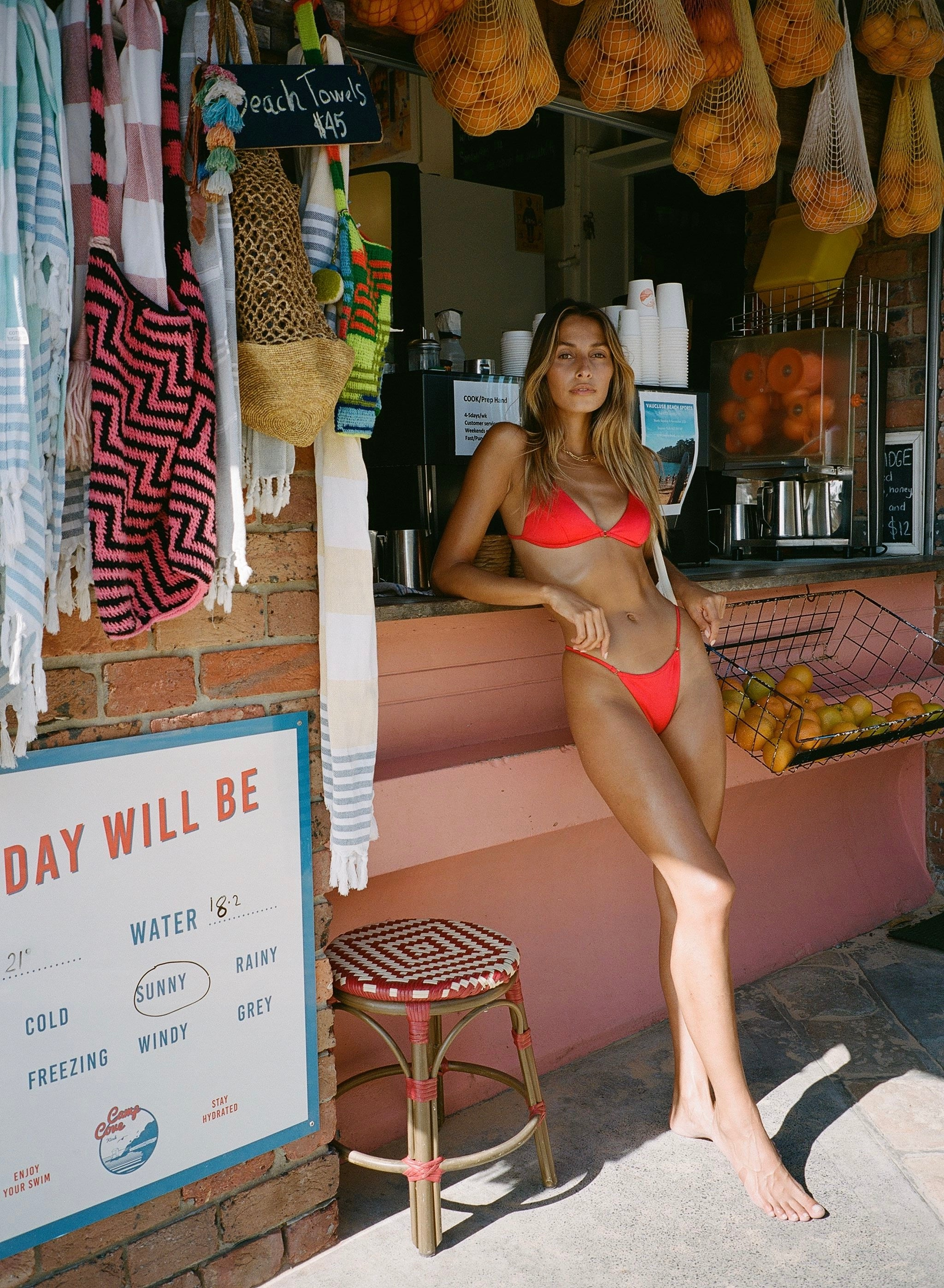 Model Dominique Elissa wearing the sommer swim red bralette bikini top and matching bottoms at camp cove in Sydney