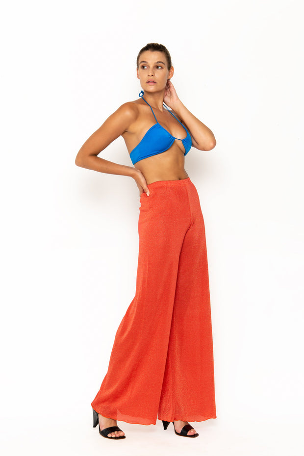 Sommer Swim model facing sideways to the right and wearing Calvi Lounge pant in Campari