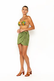 Sommer Swim model facing forwards to the right and wearing Salinas mini wrap skirt in Campari