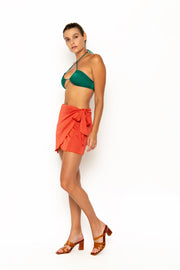 Sommer Swim model facing sideways to the right  and wearing Salinas mini wrap skirt in Campari