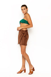 Sommer Swim model facing forwards to the right and wearing Salinas mini wrap skirt in Cinnamon
