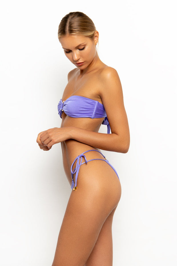 Side view of Sommer Swim model wearing the Dulce Tie Side Brazilian Bikini Bottom in colour Provenza