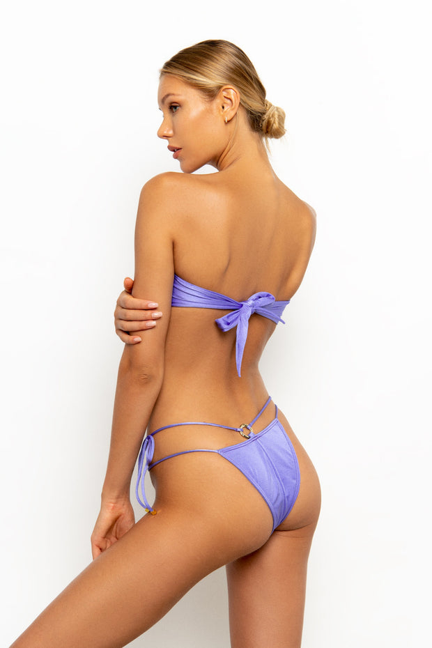 Back view of Sommer Swim model wearing the Dulce Tie Side Brazilian Bikini Bottom in colour Provenza with gold ring detail back