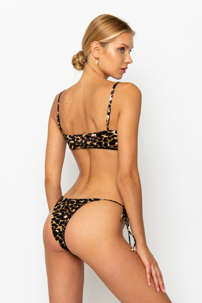 Sommer Swim model facing backwards and wearing a Cara brazilian bikini bottom in Leopard Luxe