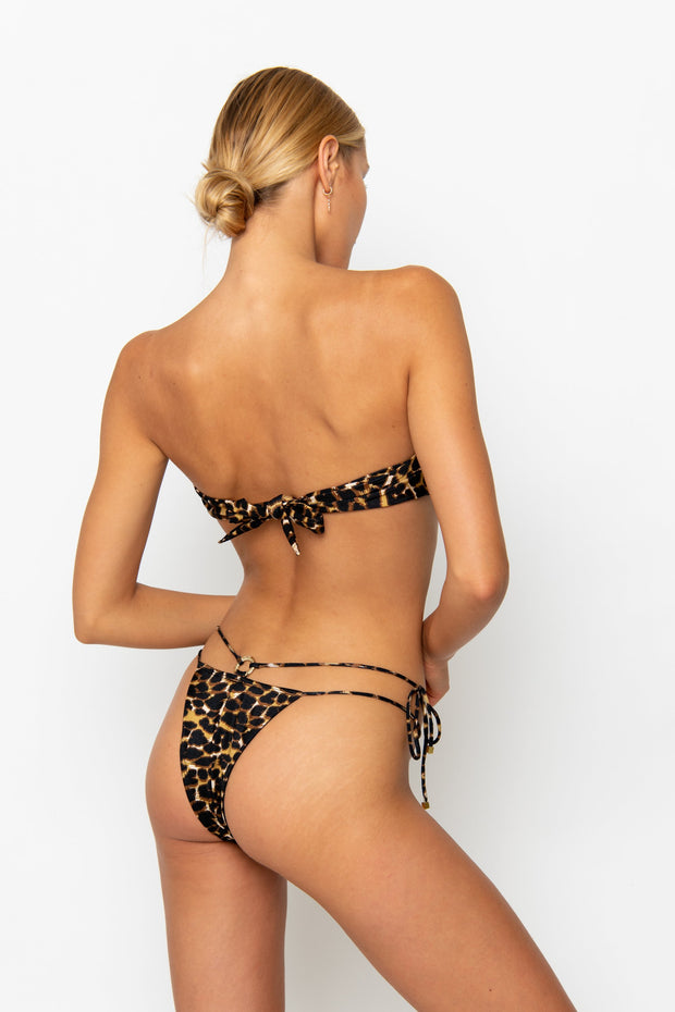 Sommer Swim model facing backwards and wearing a Dulce brazilian cut bikini bottom in Leopard Luxe