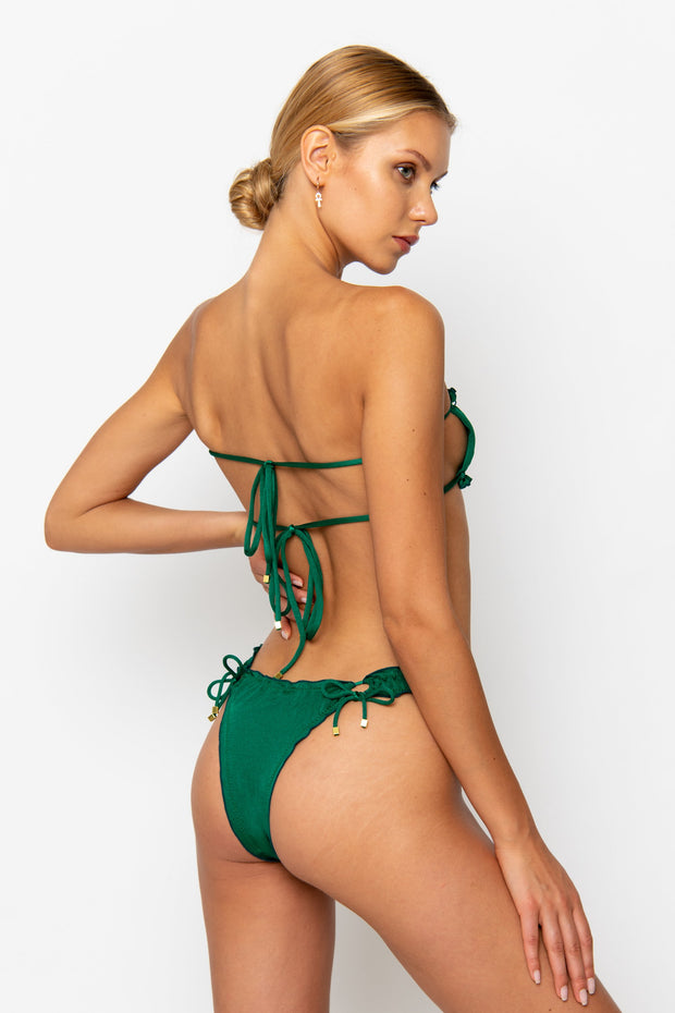 Sommer Swim model facing backwards wearing Esmee adjustable halter style bikini top in emerald