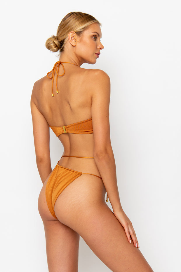 Sommer Swim model facing backwards to the right and wearing a Naomi tie side bikini bottom in Papagayo