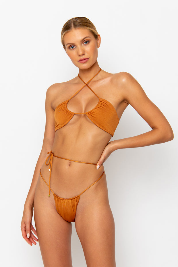 Sommer Swim model facing backwards leaning on the hip and wearing a Naomi tie side bikini bottom in Papagayo