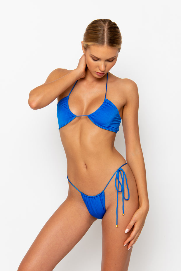 Sommer Swim model facing forwards looking down and wearing a Naomi tie side bikini bottom in Sirius