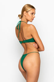Sommer Swim Model facing backwards and wearing a Xena halter style top in Emerald