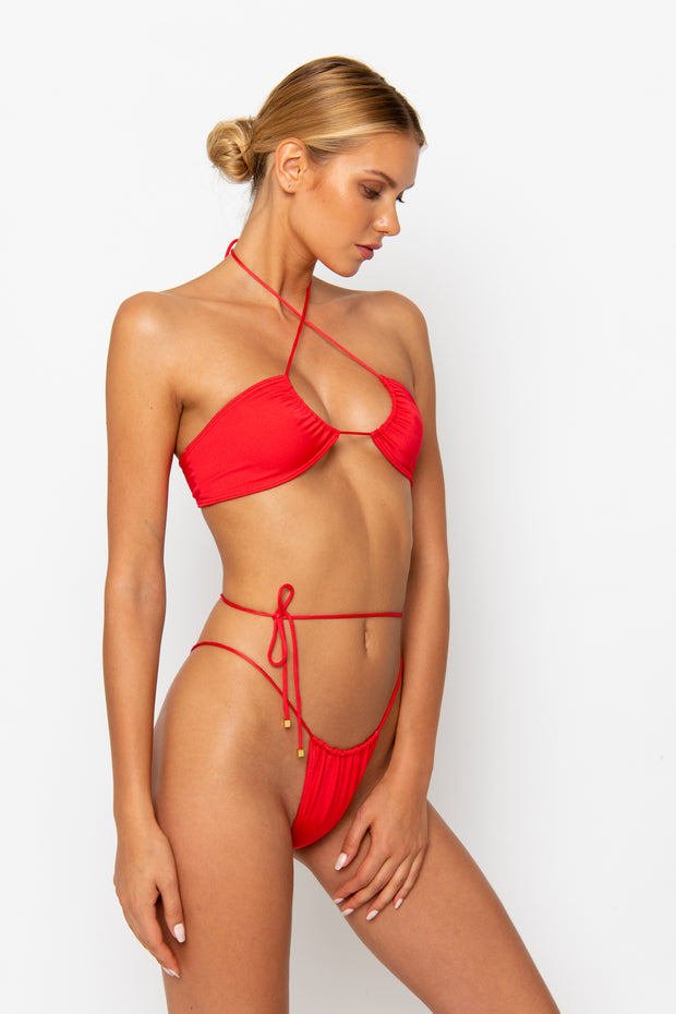 Sommer Swim Model facing sideways to the left and wearing a Xena halter style bikini top in Venere