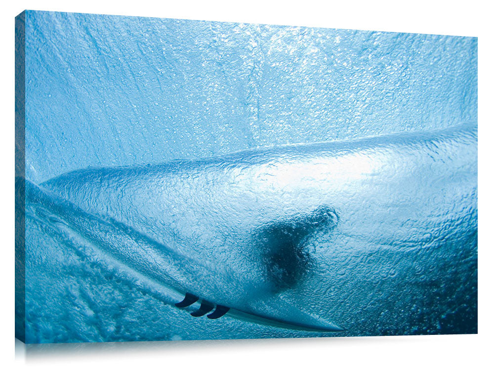 A behind the wave, underwater view of a surfer in the tube.